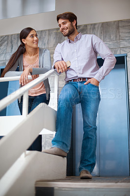 Buy stock photo Shot of two coworkers chatting together at the office stairs