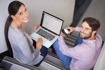 Buy stock photo Portrait of two young office workers sitting in a stairwell using a laptop