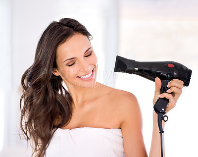 Buy stock photo A beautiful woman drying her hair with a hairdryer