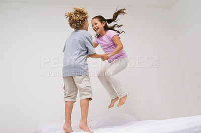 Buy stock photo Shot of two little children jumping on a bed together