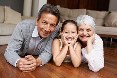 Buy stock photo A girl lying down and smiling at the camera with her grandparents
