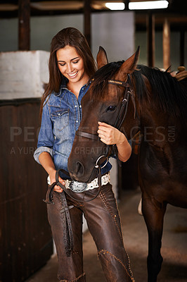 Buy stock photo A young woman in a stable with her horse