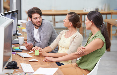 Buy stock photo Shot of a group of young businesspeople talking at their desk