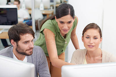 Buy stock photo Shot of a young businesswoman showing something to her colleagues on the computer