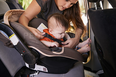 Buy stock photo Cropped shot of a baby boy being put into his car seat