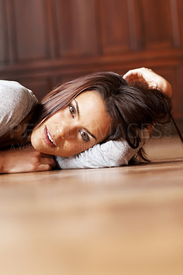 Buy stock photo Thoughtful young woman lying on floor