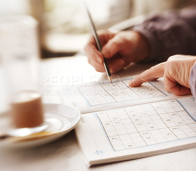 Buy stock photo Woman trying to solve Sudoku Puzzle - window, sunlight, and coffee