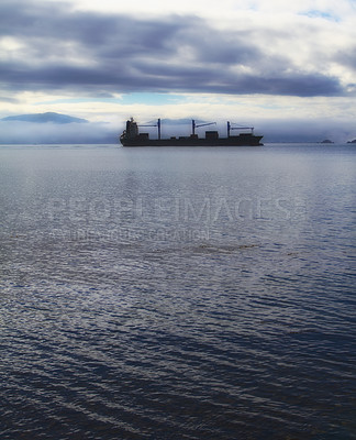 Buy stock photo A photo of a cargo ship early morning