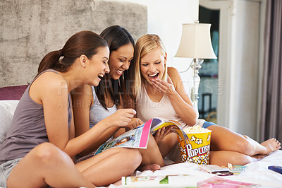 Buy stock photo Shot of a group of friends browsing through magazines at home