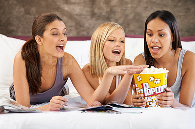 Buy stock photo Shot of a group of young women hanging out at home with some popcorn