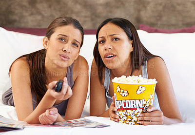 Buy stock photo Two attractive young women looking sad while watching a movie together at home