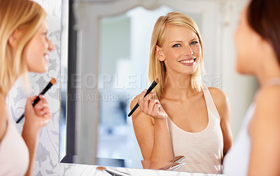 Buy stock photo Shot of a young woman applying makeup in front of a mirror as her friend stands by
