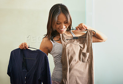 Buy stock photo Shot of an attractive young woman deciding what to wear
