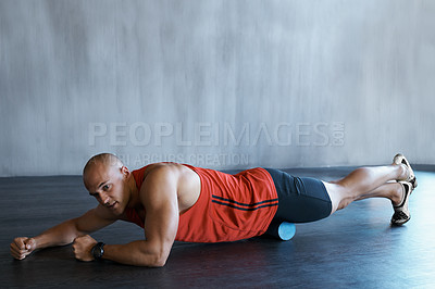 Buy stock photo A young man doing a workout with a foam roller