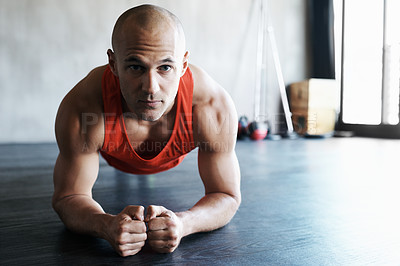 Buy stock photo Shot of a man doing plank exercises at the gym