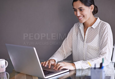 Buy stock photo Shot of a beautiful young woman working on her laptop