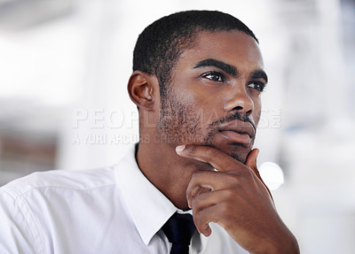 Buy stock photo Shot of a young businessman looking thoughtful