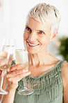 Happy senior woman enjoying a glass of champagne