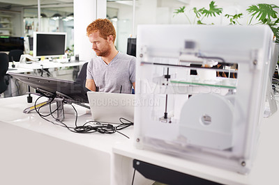 Buy stock photo A shot of a young man printing his designs on a 3D printer