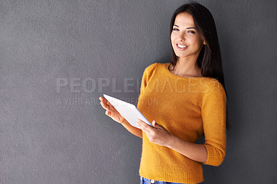 Buy stock photo Shot of an attractive young woman holding a digital tablet
