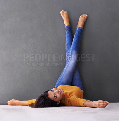 Buy stock photo Shot of an attractive young woman lying on the floor with her feet against the wall