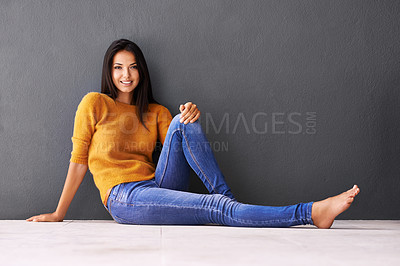 Buy stock photo Portrait of an attractive young woman sitting on the floor against a gray wall