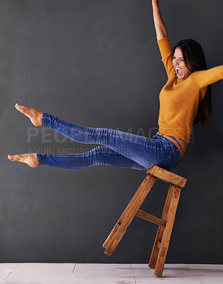 Buy stock photo Shot of a happy young woman shouting while leaning back on a stool