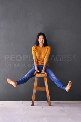 Buy stock photo An attractive young woman sitting playfully on a stool against a gray wall