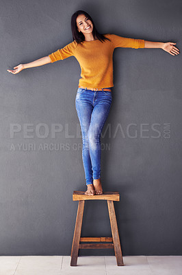 Buy stock photo An attractive young woman standing on a stool with her arms outstretched