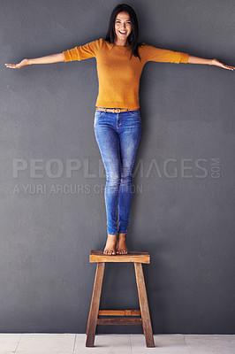 Buy stock photo Portrait of an attractive young woman standing on a stool against a gray wall