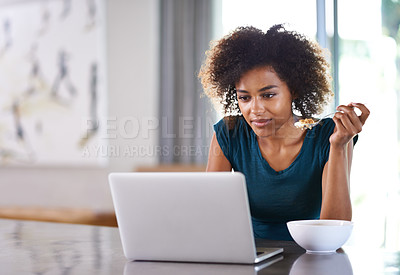 Buy stock photo Shot of a busy young woman eating breakfast while surfing the net