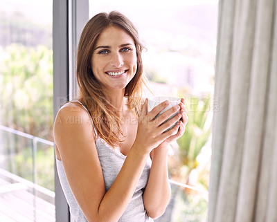 Buy stock photo Shot of an attractive young woman standing by the sliding door while enjoying a cup of coffee