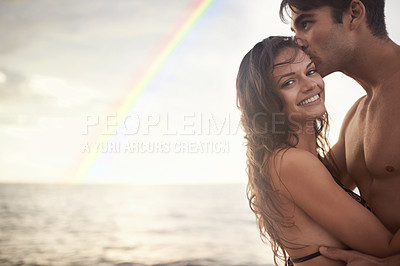 Buy stock photo Portrait of an intimate young couple enjoying a vacation by the sea at sunset