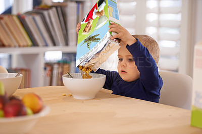 Buy stock photo Cropped shot of a young boy pouring his breakfast into a bowl at home