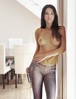 Buy stock photo Portrait of an attractive young woman with a see-through shirt standing in a doorway