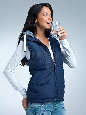Buy stock photo A studio shot of a beautiful woman drinking a glass of water