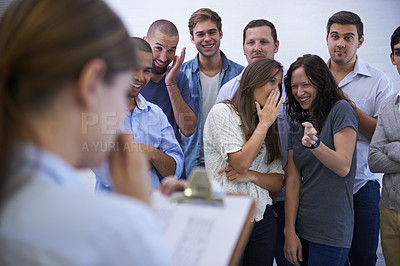 Buy stock photo Shot of an anxious young woman facing her mocking coworkers