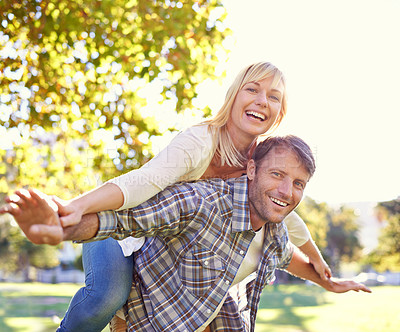 Buy stock photo Shot of a happy man piggybacking his wife