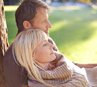 Buy stock photo Cropped shot of an attractive couple relaxing in the park