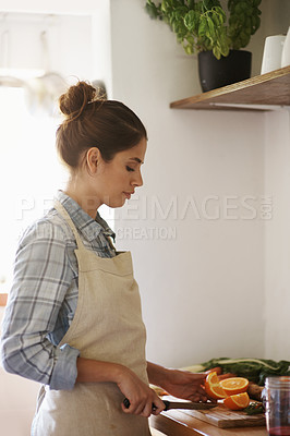 Buy stock photo Shot of a beautiful young woman wearing preparing healthy food in the kitchen