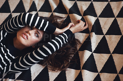 Buy stock photo Cropped high angle shot of an attractive young woman lying on a rug