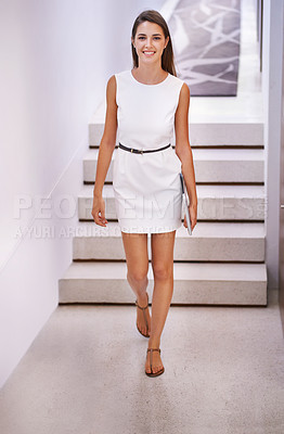 Buy stock photo Portrait of an attractive young businesswoman walking down a corridor with her digital tablet