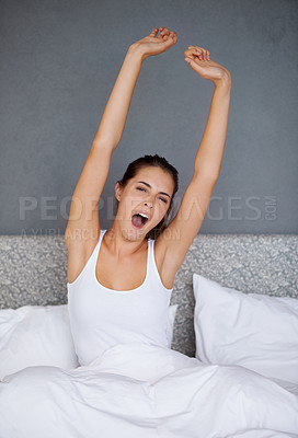 Buy stock photo Shot of a young woman stretching her arms and yawning upon waking up