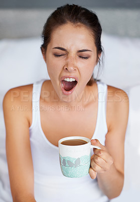 Buy stock photo A young woman giving a big yawn while sitting with a cup of coffee in bed