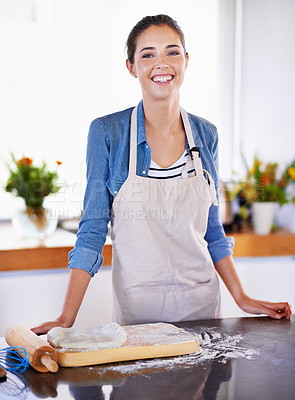 Buy stock photo A portrait of a happy young woman baking in her kitchen