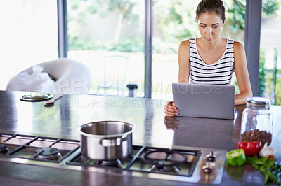Buy stock photo A beautiful young woman browsing the internet for recipes in her kiitchen