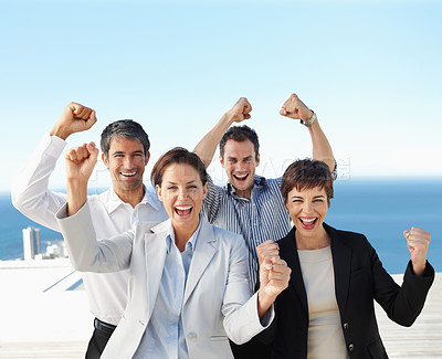 Portrait of a group of excited business colleagues with their hands raised