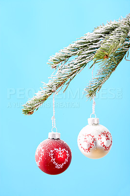 Buy stock photo Christmas decorations hanging from a tree branch, isolated on blue- copyspace