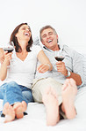 Laughing mature couple lying on their bed enjoying a glass of wine
