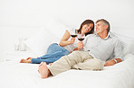 Happy mature couple lying on their bed having a glass of wine